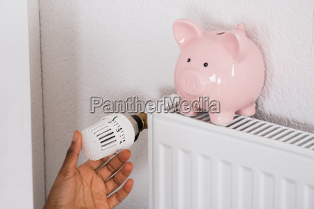 womans hand adjusting thermostat with piggy