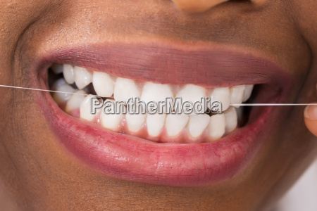 african woman flossing teeth