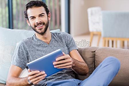 handsome man using tablet smiling at