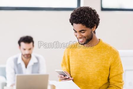 smiling, man, holding, document, using, smartphone - 16747312