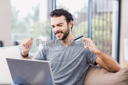 happy man holding credit card and