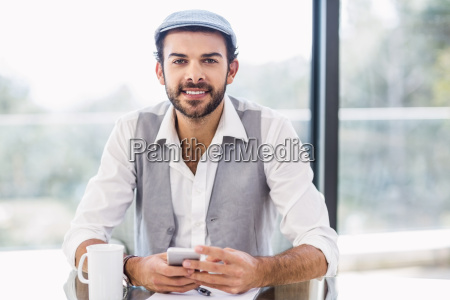 handsome man using smartphone smiling at