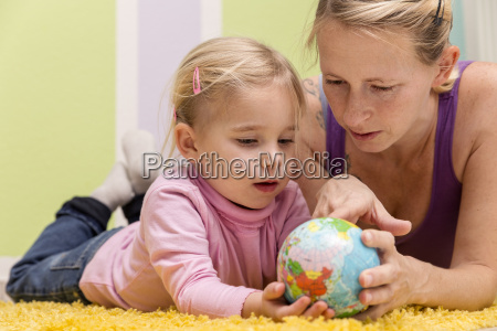 mother and daughter with small globe