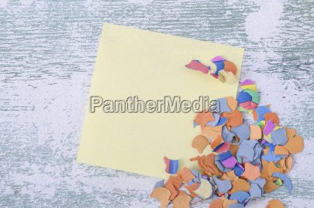 blank adhesive note and confetti on