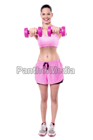 active young woman posing with dumbbells