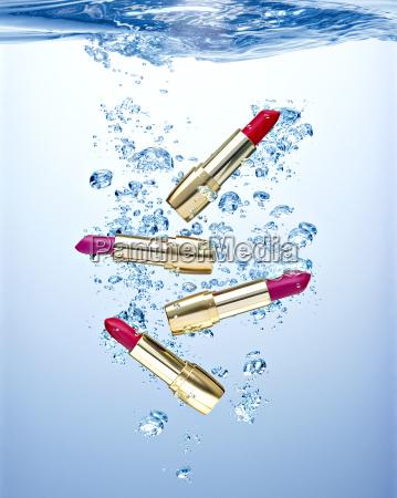 four waterproofed lipsticks under water