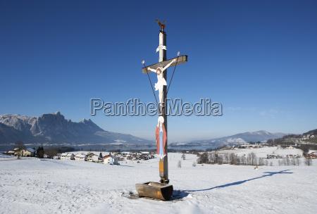 austria salzkammergut crucifix in winter landscape
