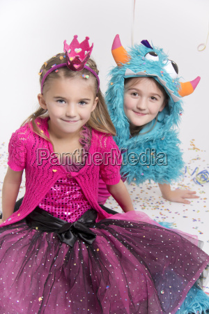 two smiling girls masquerade as a