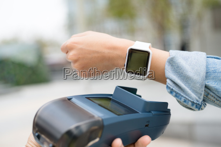 customer using wearable watch to checkout