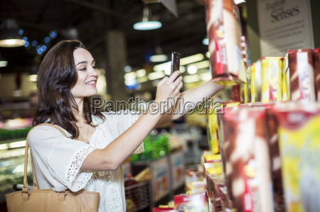 woman at supermarket scanning prices with