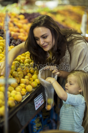 mother and daughter at supermarket shopping