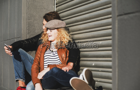 relaxed young couple sharing cell phone