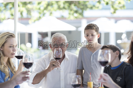 extended family drinking red wine at