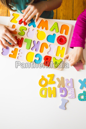 two sisters with with wooden alphabet
