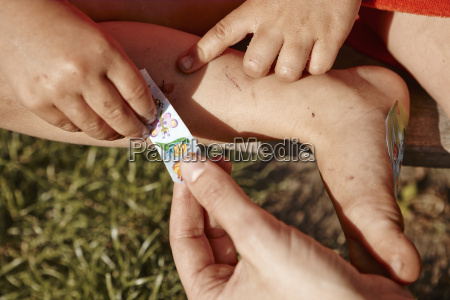mother attaching plaster on daughters leg