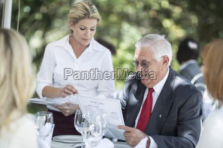waitress explaining menu to clients at