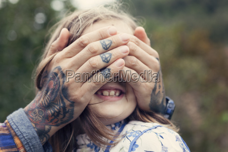mans tattooed hands covering eyes of