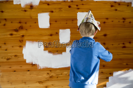 boy painting smiley face on wooden