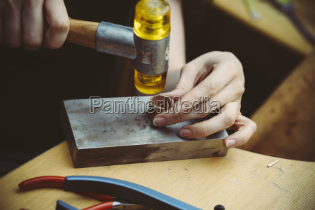 goldsmith working with rubber mallet on