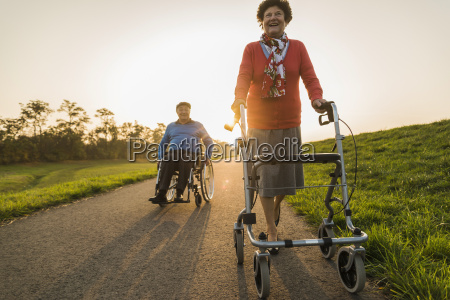 smiling senior couple with wheelchair and
