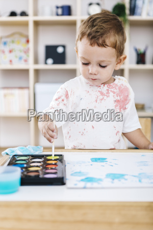 portrait of little boy painting with