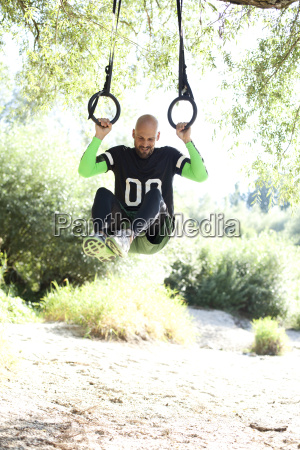 man doing crossfit exercise on rings
