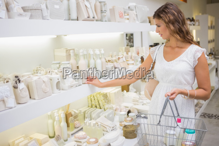 focused woman with shopping basket browsing