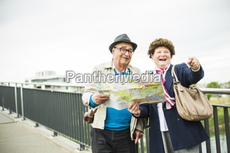 senior couple with map standing on