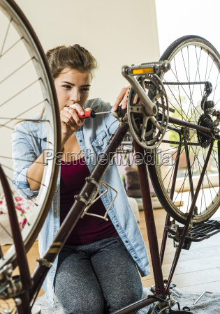 young woman at home repairing her