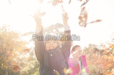 entusiasta muchacho que juega en hojas