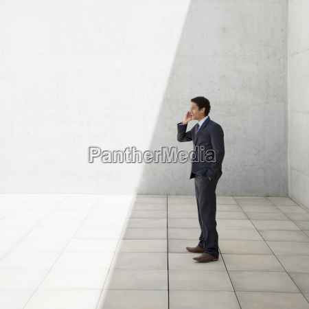 businessman standing in shade and talking