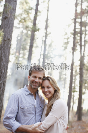 portrait of smiling couple in woods