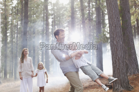 happy family playing in sunny woods