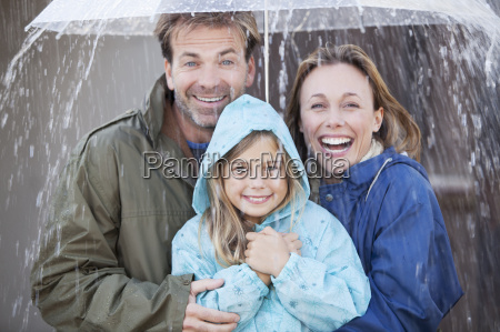 portrait of enthusiastic family under umbrella