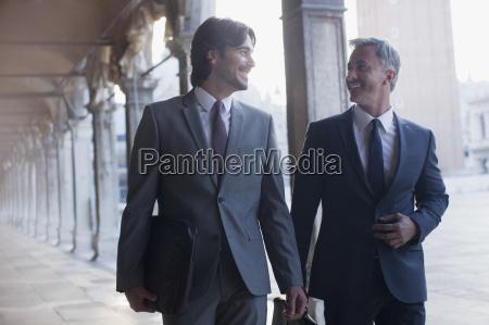 smiling businessman walking along corridor