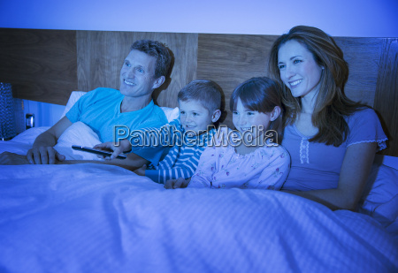 family watching television in bed