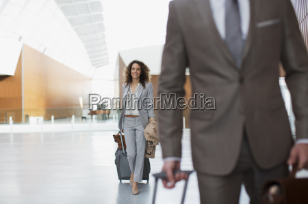 smiling businesswoman pulling suitcase in airport