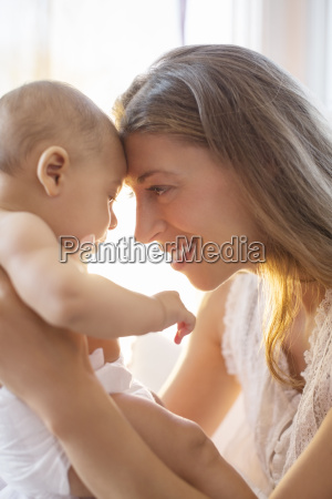 mother touching foreheads with baby boy