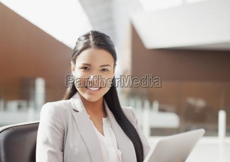 portrait of smiling businesswoman using digital