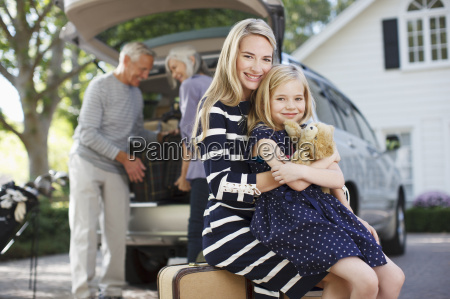 smiling mother and daughter sitting on