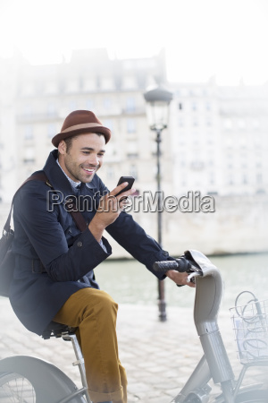businessman using cell phone on bicycle