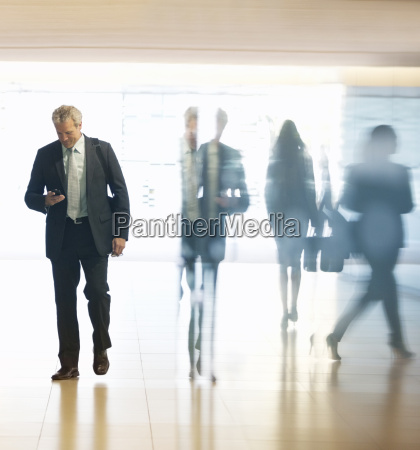 businessman checking cell phone in lobby