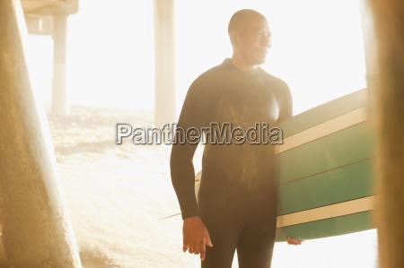 older surfer carrying board under pier