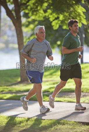 men jogging together in park