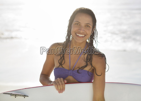 portrait of smiling woman holding surfboard
