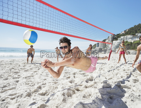 man diving for volleyball on beach