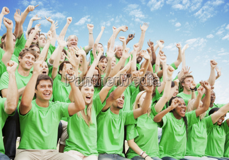 crowd in green t shirts cheering