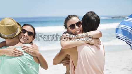 happy couples hugging at beach