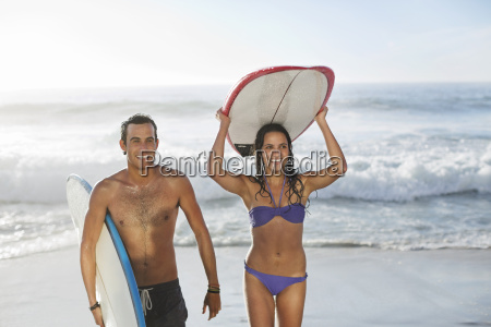 happy couple carrying surfboards at beach