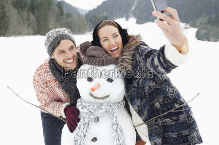 enthusiastic couple taking self portrait with